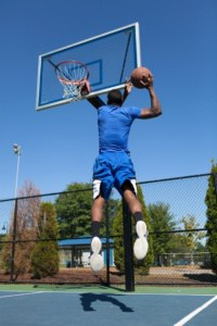 man dunking on outdoor in-ground hoop